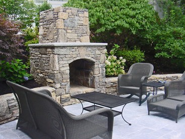 Fieldstone fireplace with travertine mantle and arched box. Fireplace, patio and sitting wall by New View