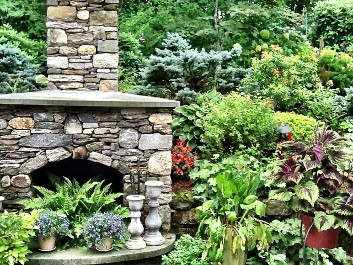 Fieldstone fireplace with angled blue stone mantle, raised hearth with arched opening and landscape by New View