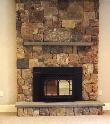 Interior Fieldstone Fireplace Veneer with Blue Stone Mantle, Raised Hearth and Wood Stove Insert by New View